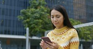 Woman check on smart phone in city