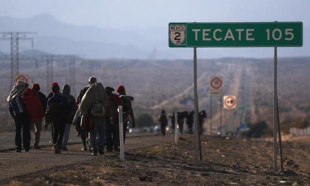 migrant caravan migrants walk to Tijuana