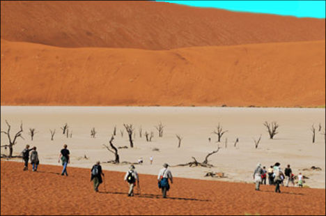 visitors descending into the white sandy pan