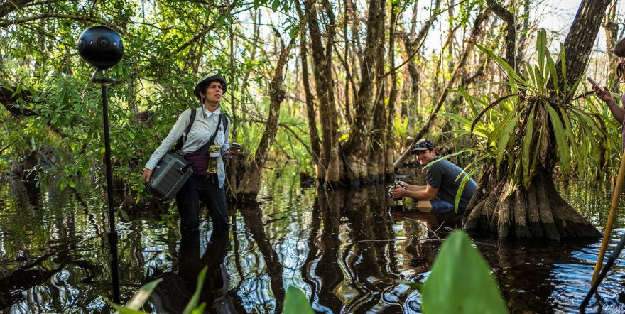 image of Liz Miller and colleague in swamps with film gear