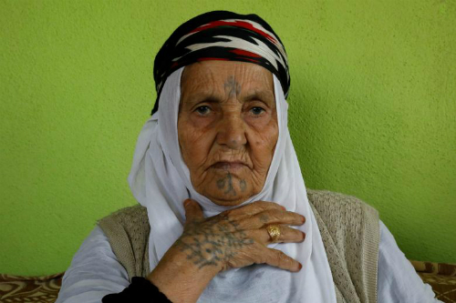 Ayse Yusufoglu, 84, poses as she speaks about her tattoos at her home in Alakus village near Kiziltepe, a town in southeastern province of Mardin, Turkey,