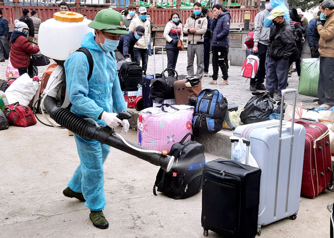 A medical staff disinfects luggage of Vietnamese workers, Ha Tinh Province January 17 2021. Photo by VnExpress/Duc Hung.