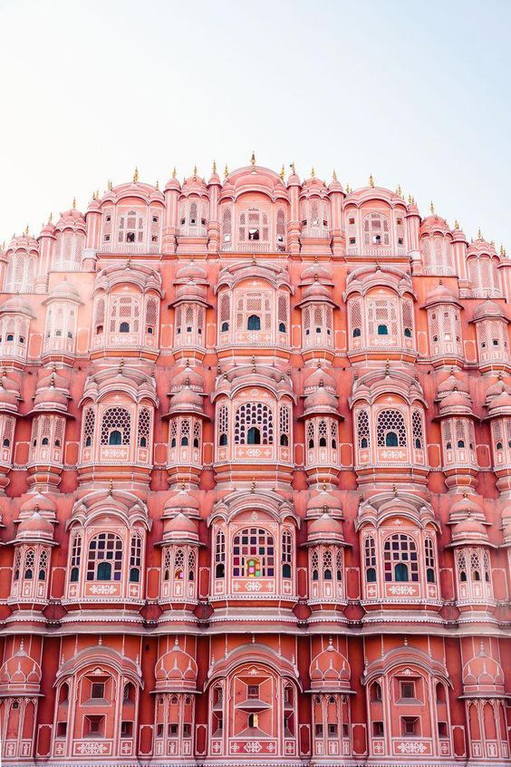 How to explore the colourful city of Jaipur like a travel photographer. Here, outside the Hawa Mahal, an entirely pink building in India. #adventuretravel