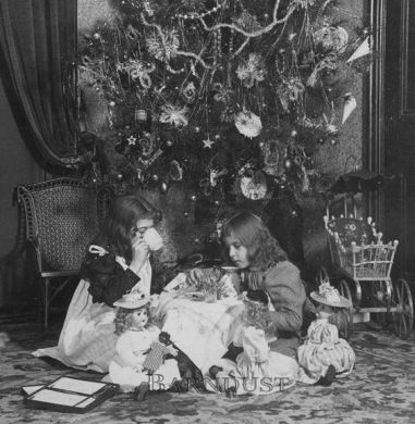 A stereoview photograph showing two girls having tea with their dolls underneath a Christmas tree, ca. 1896. By the Keystone View Company,…