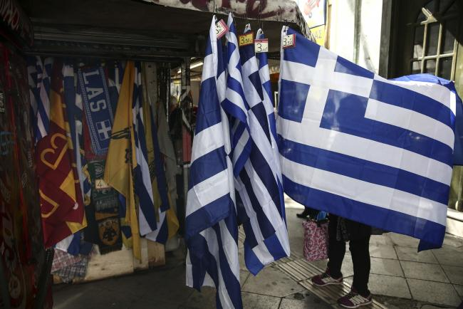 © Bloomberg. A woman unfolds a souvenir Greek national flag hanging outside a street vendor's kiosk in Athens, Greece, on Tuesday, Feb. 28, 2017. Greeces auditors are pulling together a list of policies the country needs to implement to unlock additional bailout funds as talks with Athens resumed on Tuesday, two people familiar with the matter said.