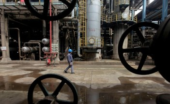 © Reuters. A worker walks past oil pipes at a refinery in Wuhan