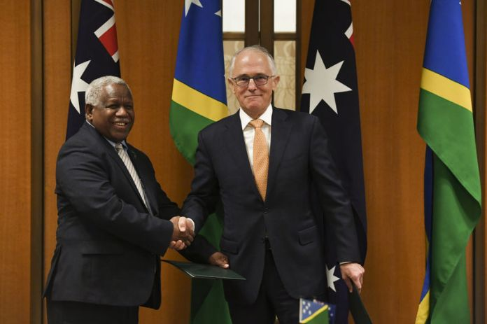 © Reuters. Prime Minister of the Solomon Islands Rick Houenipwela and Australian Prime Minister Malcolm Turnbull shake hands during a signing ceremony at Parliament House in Canberra