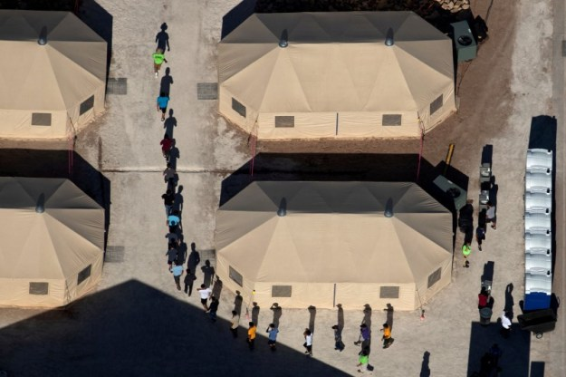 © Reuters. FILE PHOTO: Immigrant children are led by staff in single file between tents at a detention facility in Tornillo, Texas