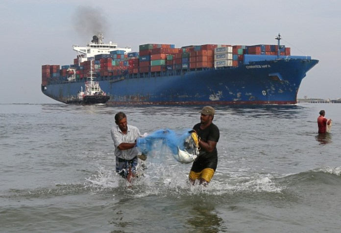 © Reuters. FILE PHOTO: Fishermen carry bluefin trevally fish locally known as Vatta as a cargo ship carrying containers moves in the Arabian Sea in Kochi,