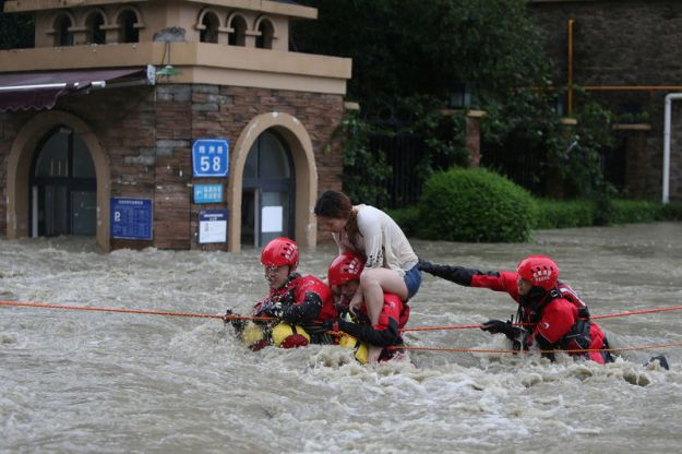 © Reuters. Firefighters rescue a stranded woman on a flooded street, following heavy rainfall in Chengdu