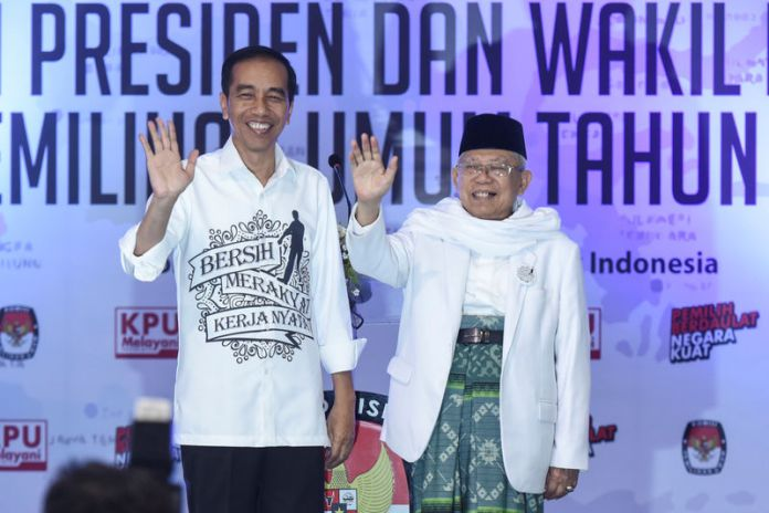 © Reuters. Indonesian President Joko Widodo and his running mate for the 2019 presidential election Islamic cleric Ma'ruf Amin wave after registering for the election at the General Election Commission in Jakarta
