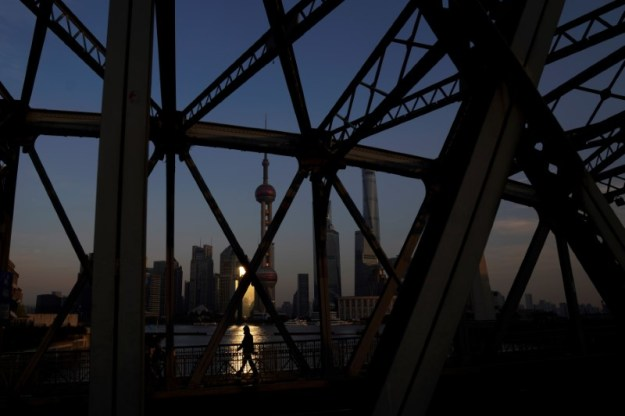 © Reuters. A man walks on a bridge in front of the financial district of Pudong in Shanghai