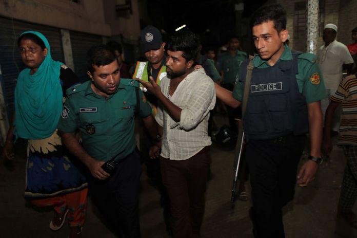 © Reuters. Police detain a man, brother of an alleged drug dealer Farhad Hossain Babu, during an anti drug raid in Dhaka