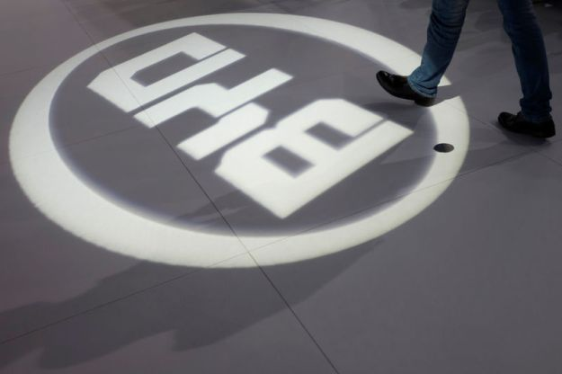 © Reuters. FILE PHOTO: A man walks past a light flashing on the floor in the shape of the logo of BYD Auto during the media preview of the 10th China International Automobile Exhibition in Guangzhou