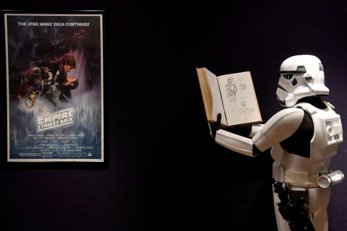 © Reuters. A man wearing a storm trooper costume stands in front of a Star Wars poster belonging to costume designer John Mollo, during a photo-call ahead of an auction at Bonhams in central London