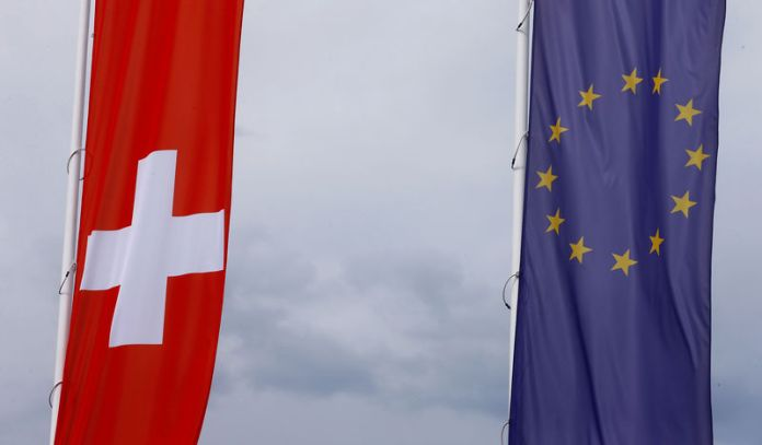 © Reuters. FILE PHOTO: Flags of the European Union and Switzerland flutter in the wind in Blotzheim