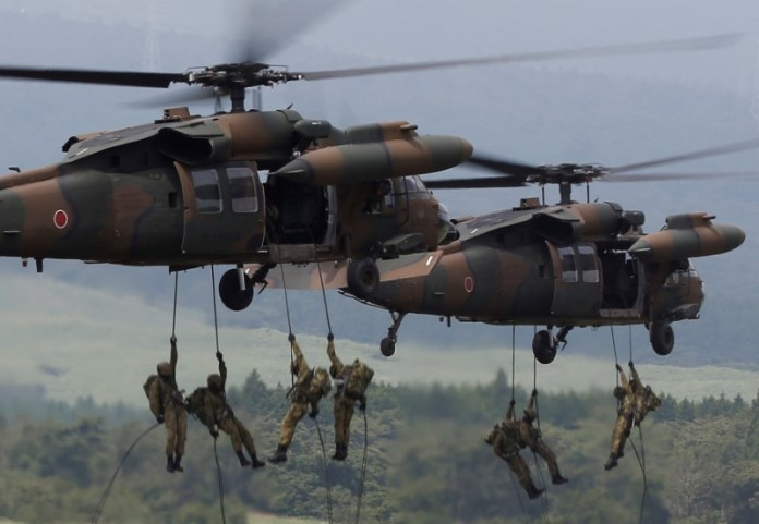 © Reuters. Japanese Ground Self-Defense Force soldiers rappel from UH-60 Black Hawk helicopters during an annual training session near Mount Fuji at Higashifuji training field in Gotemba