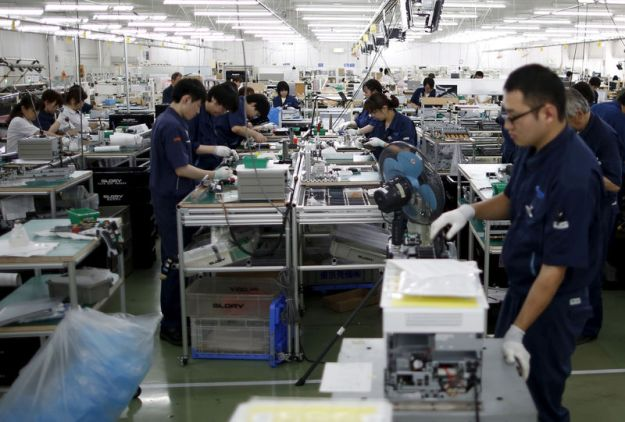 © Reuters. FILE PHOTO - Employees work an assembly line at a factory of Glory Ltd., a manufacturer of automatic change dispensers, in Kazo, north of Tokyo