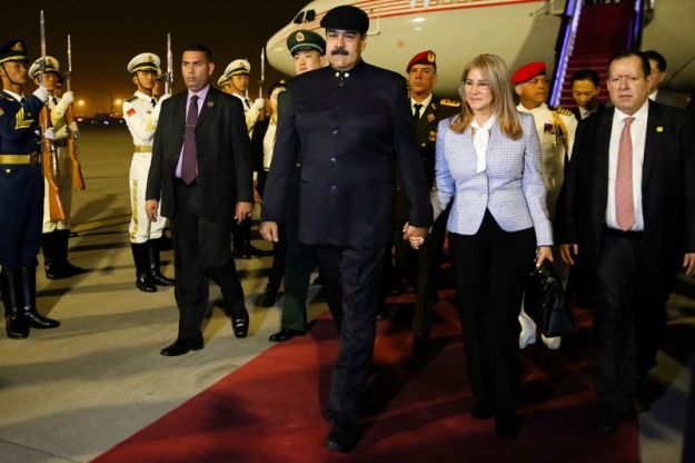 © Reuters. Venezuela's President Nicolas Maduro walks with his wife Cilia Flores upon their arrival at the airport in Beijing
