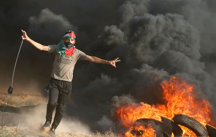© Reuters. Palestinian holds a sling to hurl stones at Israeli troops during a protest at the Israel-Gaza border fence east of Gaza City