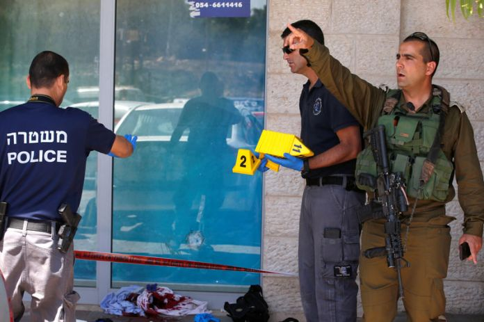 © Reuters. Israeli security personnel work at the scene of a stabbing attack near a mall in the Gush Etzion Junction in the occupied West Bank
