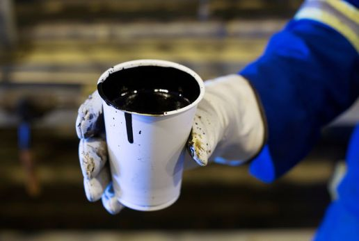 © Reuters. FILE PHOTO: A worker holds a cup of heavy oil south of Fort McMurray