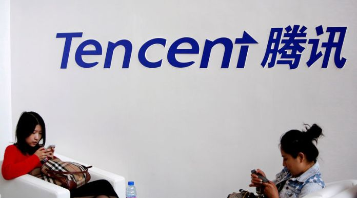 © Reuters. FILE PHOTO: Visitors use phones underneath of logo of Tencent at Global Mobile Internet Conference in Beijing