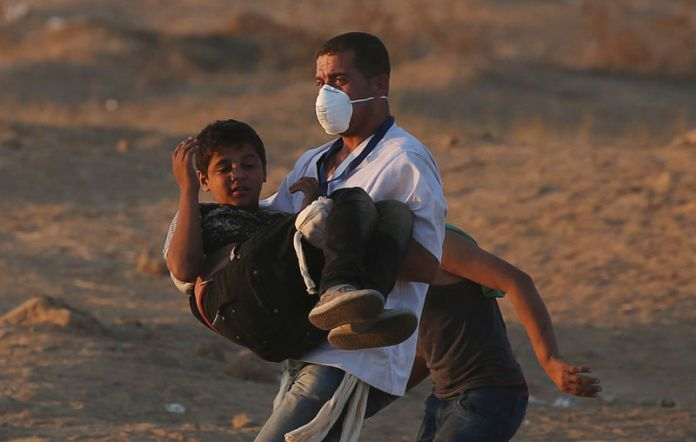 © Reuters. Wounded Palestinian boy is evacuted during a protest at the Israel-Gaza border fence in the southern Gaza Strip