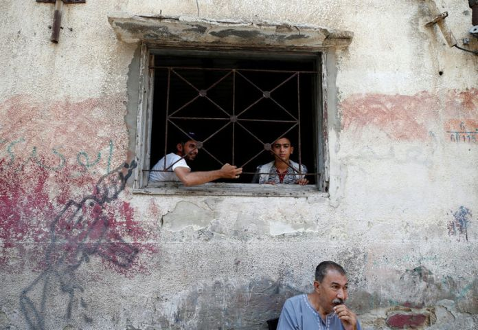 © Reuters. FILE PHOTO: Palestinians look out of their home at Al-Shati refugee camp in Gaza City
