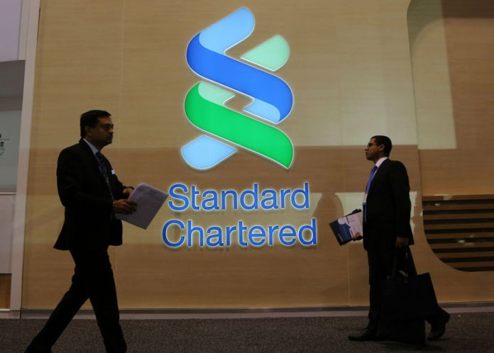 © Reuters. FILE PHOTO: People pass by the logo of Standard Chartered plc at the SIBOS banking and financial conference in Toronto