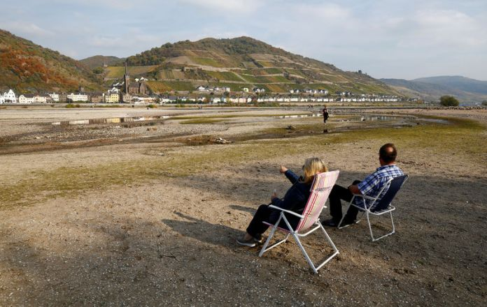 © Reuters. FILE PHOTO: A couple sit on their camping chairs amid the river bed of the dried out Rhine near Bacharach