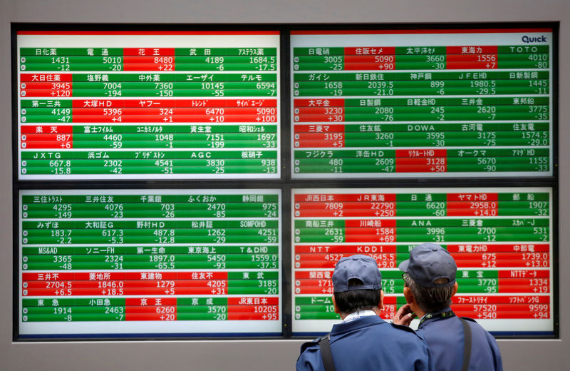 © Reuters. FILE PHOTO: Men look at stock quotation boards outside a brokerage in Tokyo