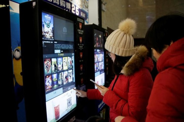 © Reuters. People print movie tickets from a machine at a cinema in Tianjin