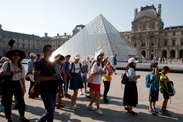 © Reuters. FILE PHOTO: Chinese tourists stand in front of the Louvre Pyramid designed by Chinese-born U.S. Architect Ieoh Ming Pei outside the Louvre Museum in Paris