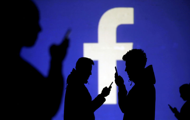 © Reuters. FILE PHOTO: Silhouettes of mobile users are seen next to a screen projection of Facebook logo in this picture illustration