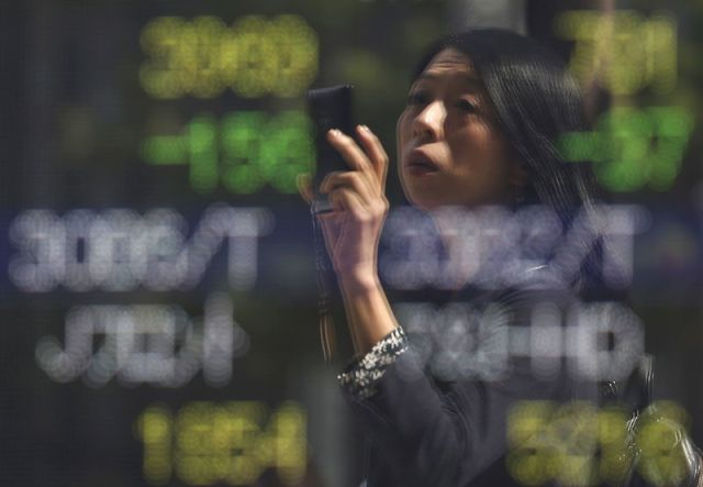 © Reuters. FILE PHOTO - A woman using a smartphone is reflected on a stock quotation board outside a brokerage in Tokyo, Japan