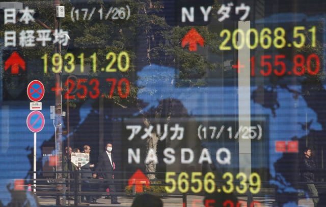 © Reuters. Pedestrians are reflected on an electronic board showing Japan's Nikkei average, the Dow Jones average and the stock averages of other countries outside a brokerage in Tokyo