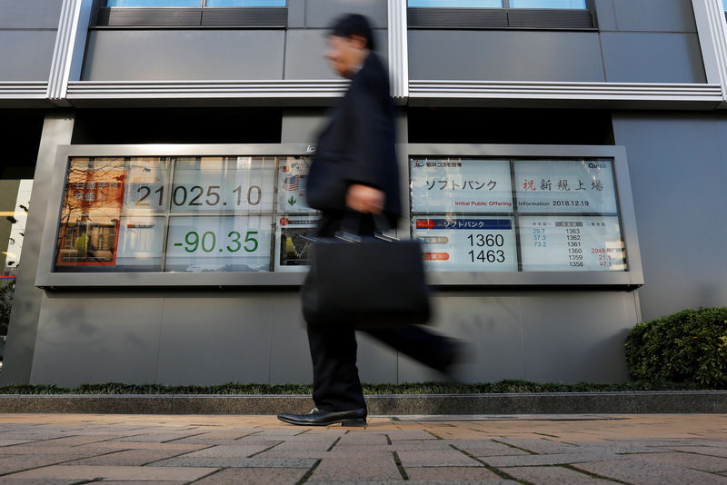 © Reuters. A man walks past in front of a stock quotation board showing the price of the SoftBank Corp. and Nikkei share average outside a brokerage in Tokyo