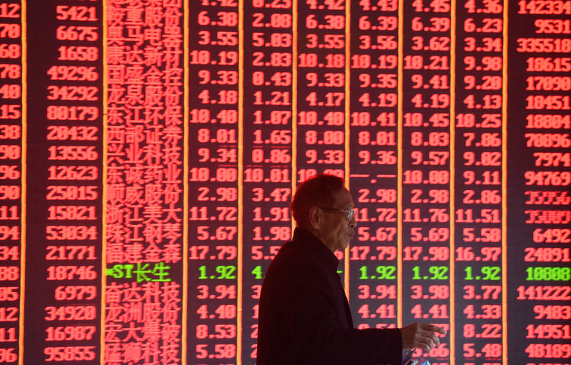 © Reuters. FILE PHOTO:  Man is seen in front of an electronic board showing stock information on the first day of trading in the Year of the Pig at a brokerage house in Hangzhou