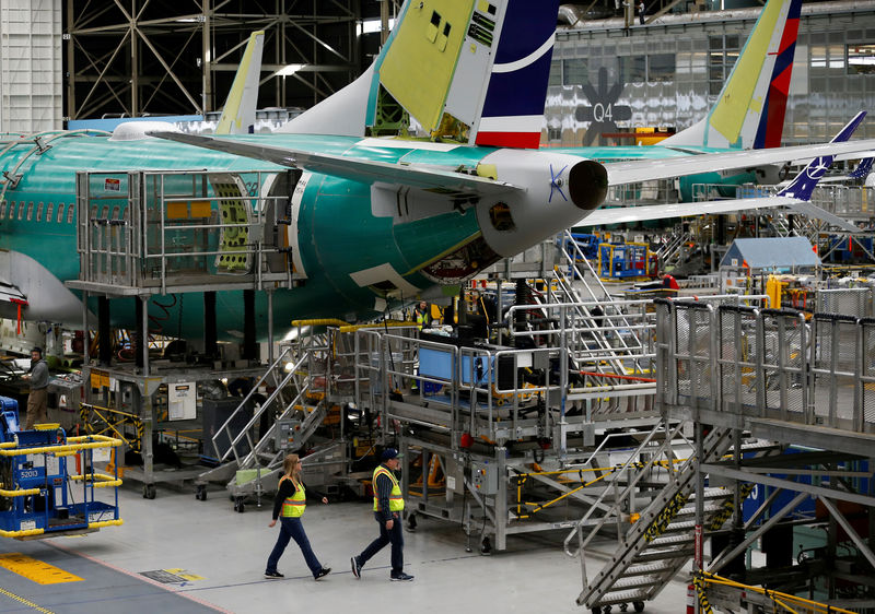 © Reuters. FILE PHOTO: Employees walk by the end of a 737 Max aircraft at the Boeing factory in Renton