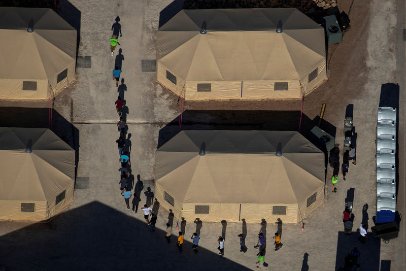 © Reuters. FILE PHOTO: Migrant children are led by staff in single file between tents at a detention facility next to the Mexican border in Tornillo