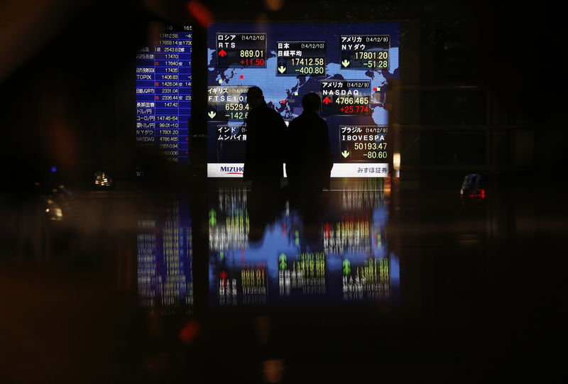 © Reuters. FILE PHOTO: Passersby are silhouetted in front of an electronic board displaying Japan's Nikkei average and various countries' stock price index outside a brokerage in Tokyo