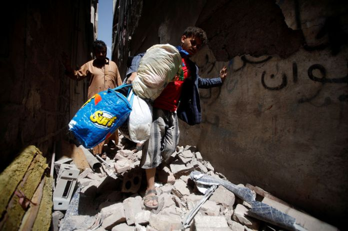 © Reuters. People carry their belongings at the site of an air strike launched by the Saudi-led coalition in Sanaa