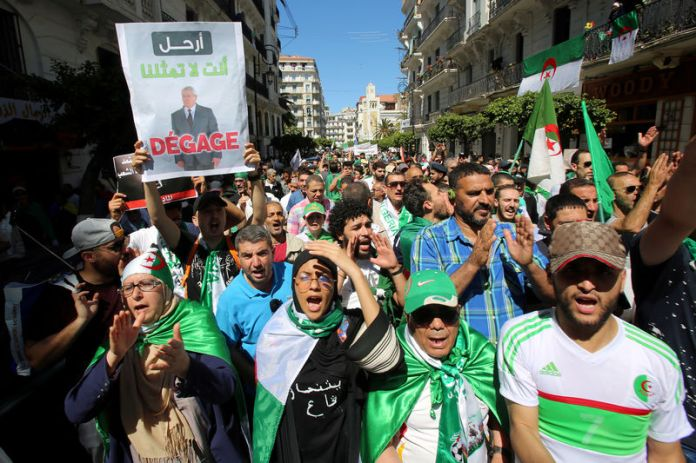 © Reuters. FILE PHOTO: A demonstrator holds a banner depicting interim president Abdelkader Bensalah during a protest demanding the removal of Algeria's ruling elite in Algiers