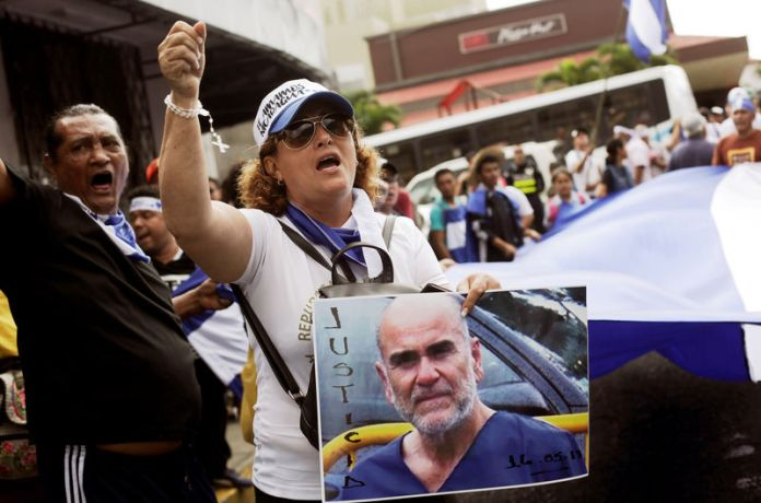 © Reuters. A Nicaraguan living in Costa Rica holds a portrait of U.S. citizen Eddy Montes while protesting in support of him in front of the Nicaragua Embassy in San Jose
