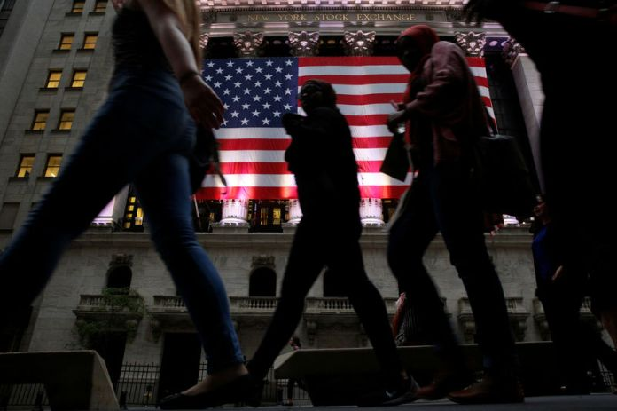 © -. FILE PHOTO: People pass by the NYSE in the financial district  of New York