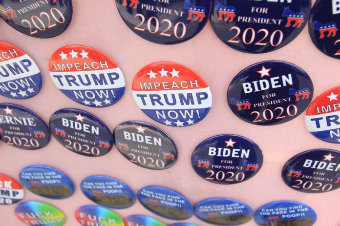 © -. FILE PHOTO: Biden for President campaign buttons and Impeach Trump Now buttons are seen for sale as U.S. Democratic presidential candidate and former Vice President Biden meets union workers campaigning for 2020 Democratic presidential nomination in Pittsb