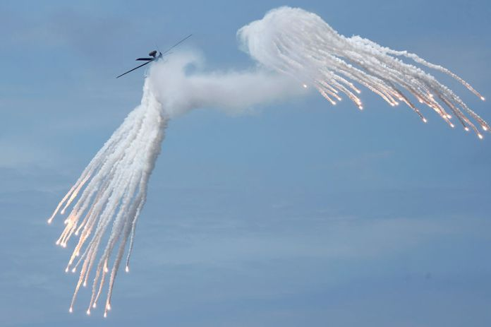 © -. An AH-1W attack helicopter releases flares during the live fire Han Kuang military exercise, which simulates China's People's Liberation Army (PLA) invading the island, in Pingtung