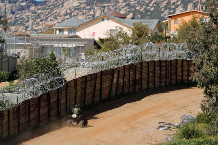 © -. A U.S. Customs and Border Patrol agent travels along the border wall between the U.S. and Mexico near Tecate, California
