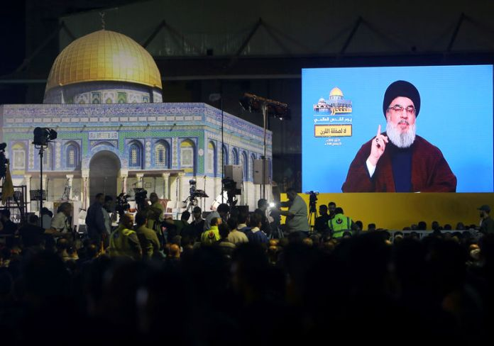 © -. Lebanon's Hezbollah leader Sayyed Hassan Nasrallah addresses his supporters via a screen during a rally marking al-Quds Day, (Jerusalem Day) in Beirut